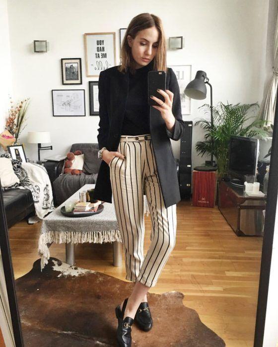 Chica usa saco y suéter negros con pantalón blanco con rayas negras