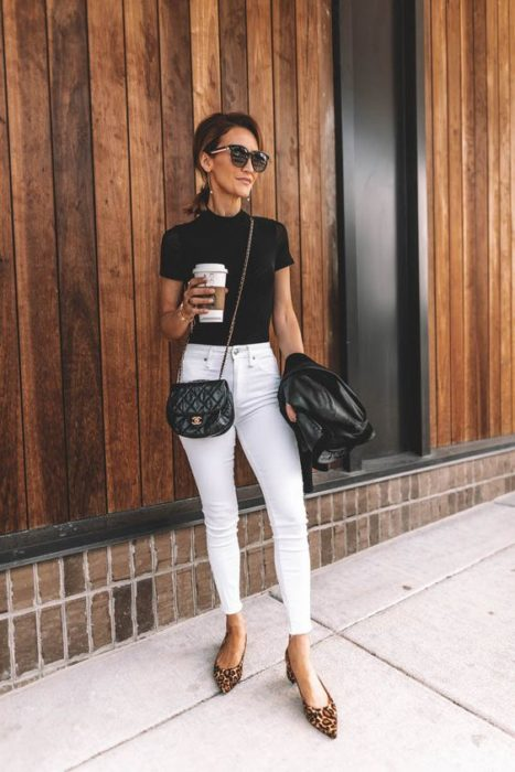 Mujer con cabello recogido y gafas obscuras usa blusa negra y pantalón blanco