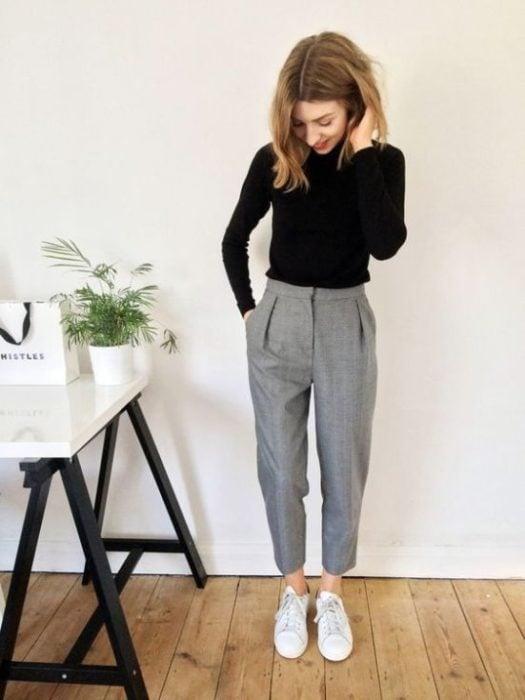 Chica de melena corta posa con mano en la cabeza y mirada hacia abajo con pantalón gris y suéter negro