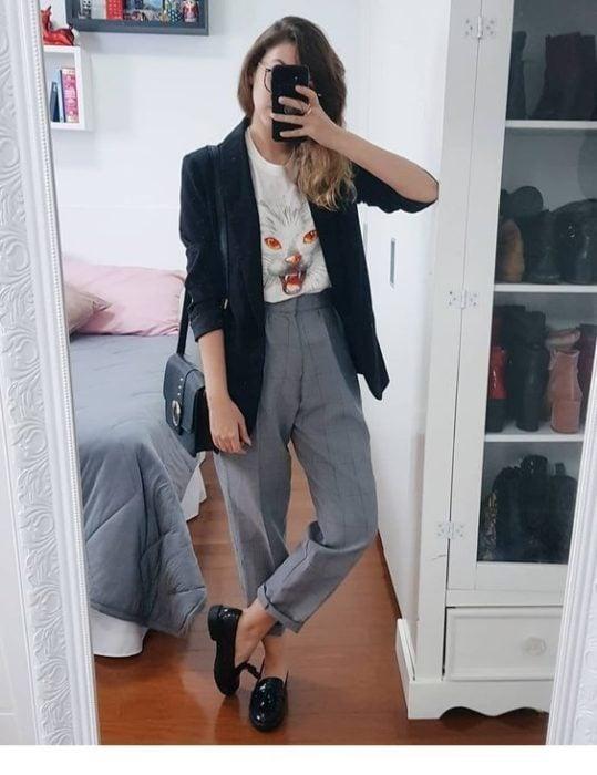 Chica se toma selfie frente al espejo con pantalón gris, saco negro y blusa blanca con estampado de gato