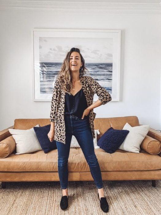 Mujer posa con mano en la cintura en la sala de su casa con saco de leopard print, blusa negra y jeans