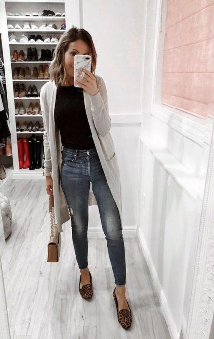 Mujer de melena corta se toma selfie con cardigan gris, blusa negra y jeans