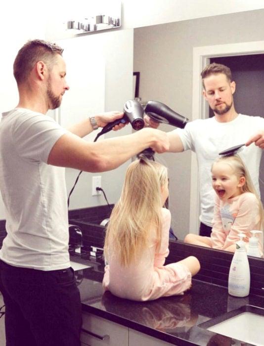 Frases del día del padre; papá peinando a su hija con secadora frente al espejo