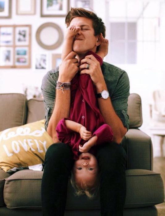 Frases del día del padre; papá jugando con su hija en la sala de estar