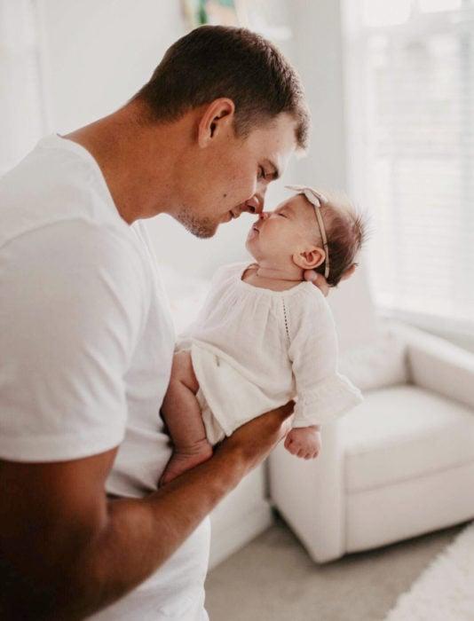 Frases del día del padre; papá cargando a su bebé recién nacida