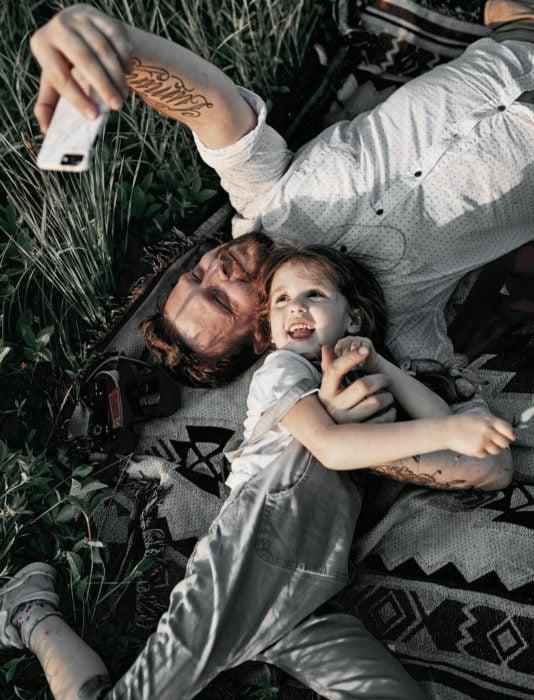 Frases del día del padre; papá e hija tomándose una selfie en el pasto