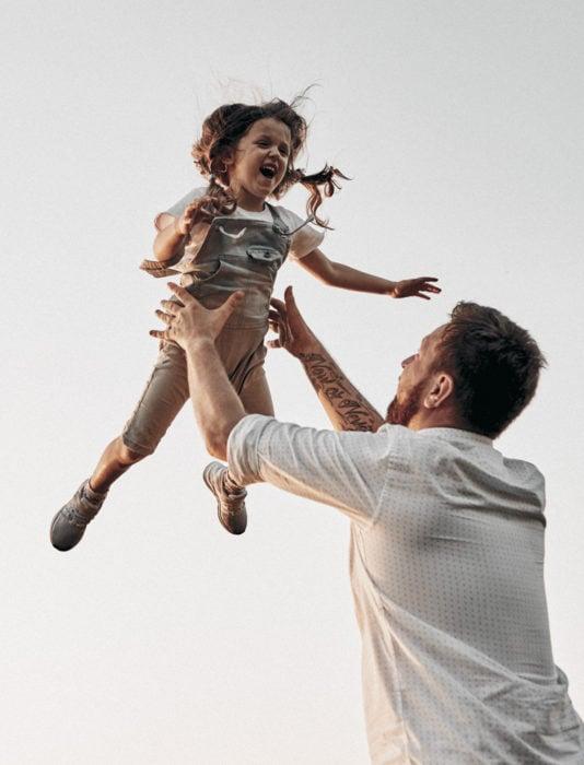 Frases del día del padre; papá jugando a lanzar a su hija en el aire