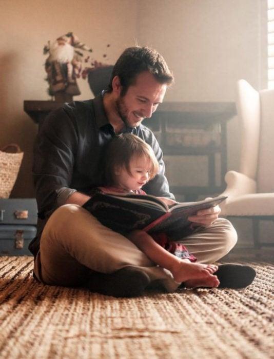 Frases del día del padre; papá leyéndole un cuento a su hija en la sala, sentados en la alfombra