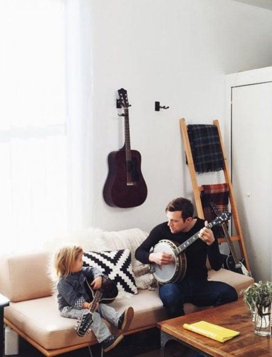 Frases del día del padre; papá e hija tocando el banjo en la sala