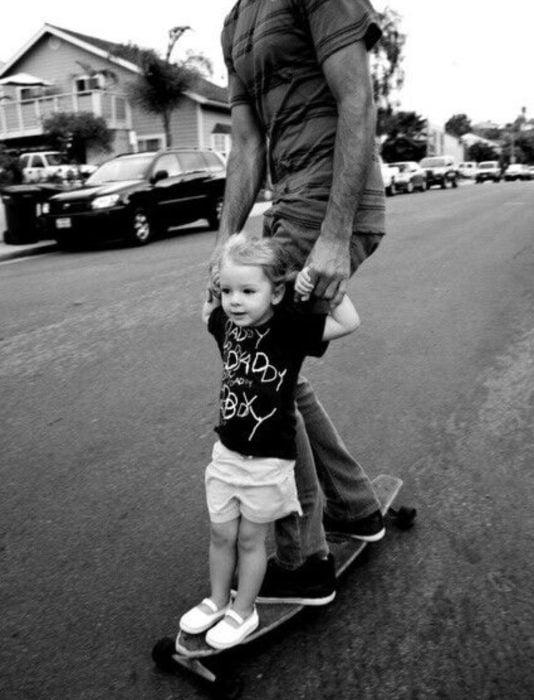 Frases del día del padre; hija y papá andando en patineta en la calle