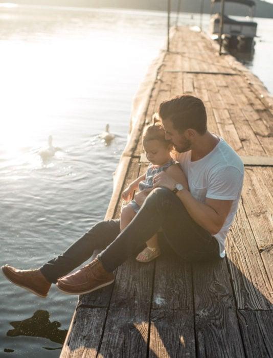 Frases del día del padre; papá e hija sentados a la orilla de un lago