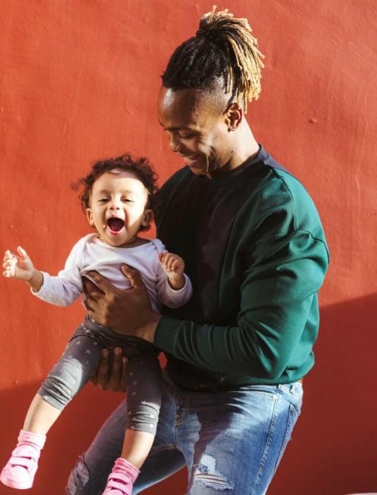 Frases del día del padre; papá abrazando y cargando a su hija bebé