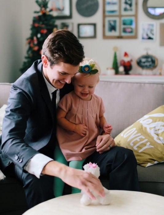 Frases del día del padre; papá e hija sonriendo sentados en el sillón mientras juegan con peluche