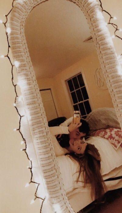 Pareja recostada tomándose fotografías a través del espejo