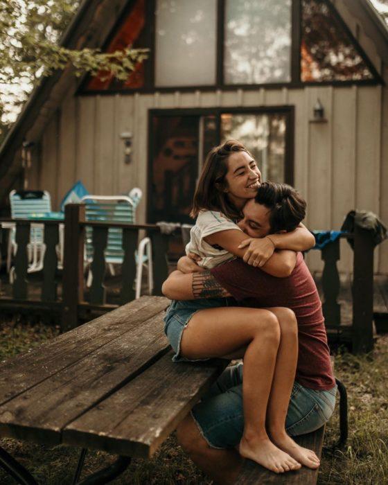 Pareja sentada en una mesa de madera abrazándose