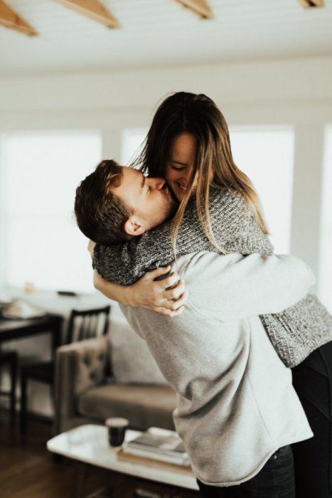 pareja abrazándose dentro de una casa
