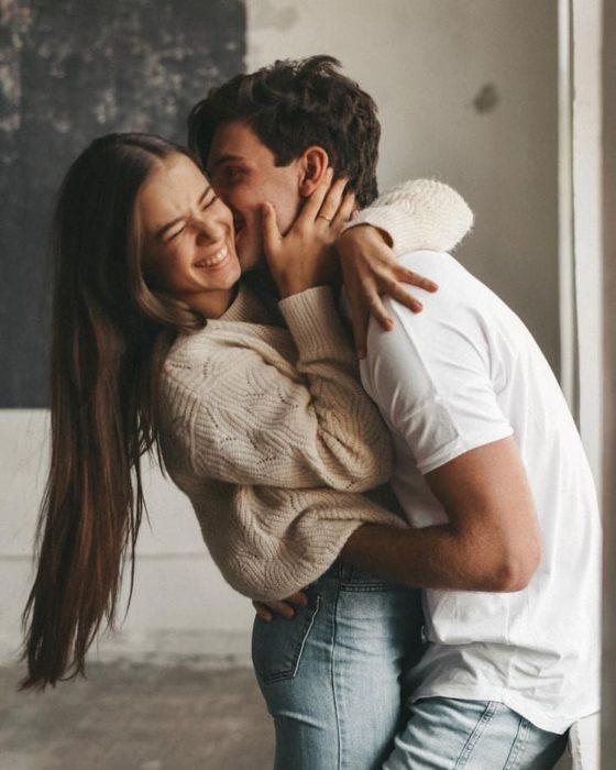 Pareja abrazándose y besándose