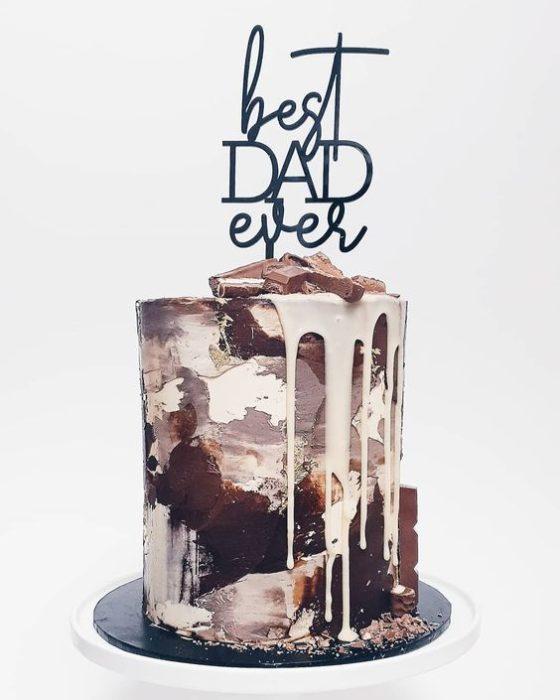 Pastel bañado de chocolates diferentes y decorado con letras abstractas de feliz día del padre