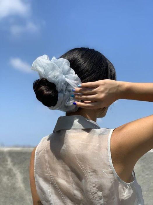 Chica con cabello negro en chongo y scrunchie gigante azul