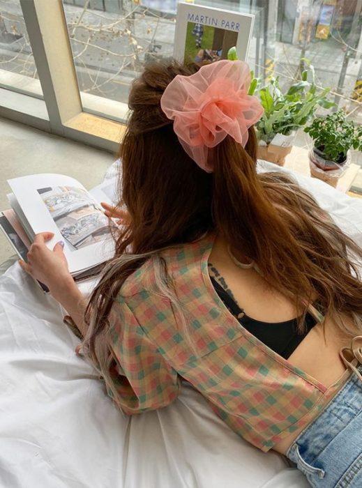 Chica acostada leyendo un libro con media coleta y scrunchie gigante rosa