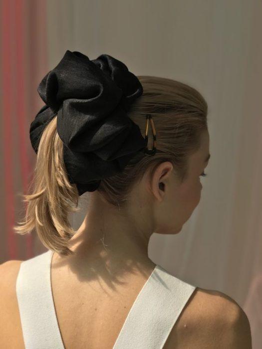 Chica rubia con coleta media y una scrunchie gigante negro