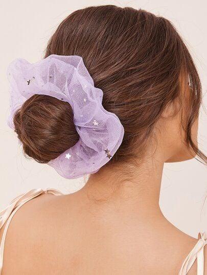 Chica de cabello castaño con chongo bajo y un scrunchie lila gigante