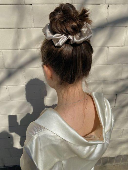 Chica de cabello castaño con chongo alto y un scrunchie gigante plateado