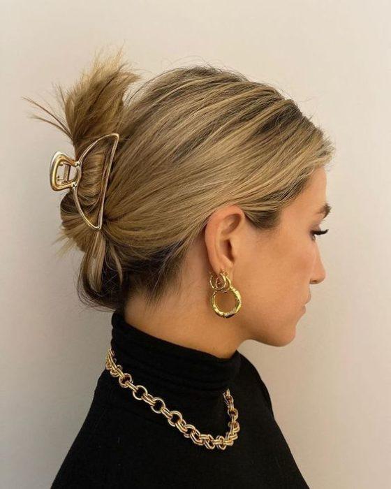 Chica rubia con recogido bajo tomado con una broche dorado