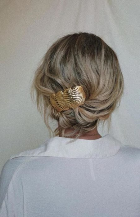 Blonde girl with tousled updo and golden brooch
