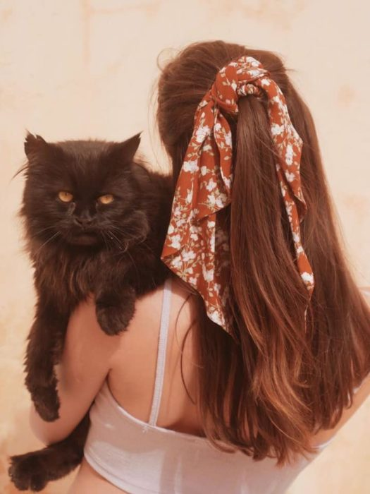 Long-haired girl in a half ponytail with an orange scarf hugs a black cat