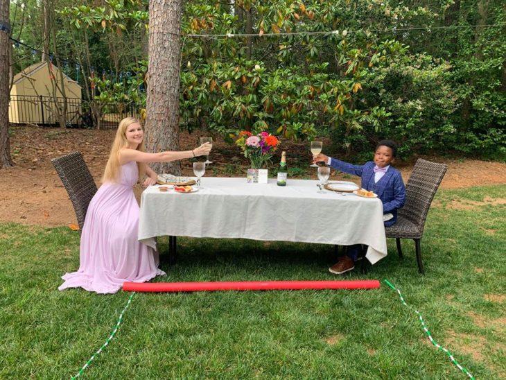 Chica y un niño comiendo en una mesa de jardín larga con un mantel blanco