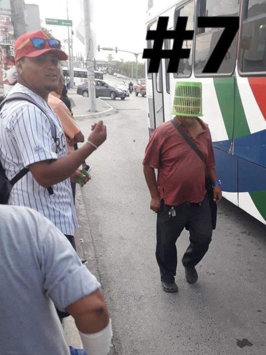 Señor usando un bote de basura en la cabeza mientras camina por la calle
