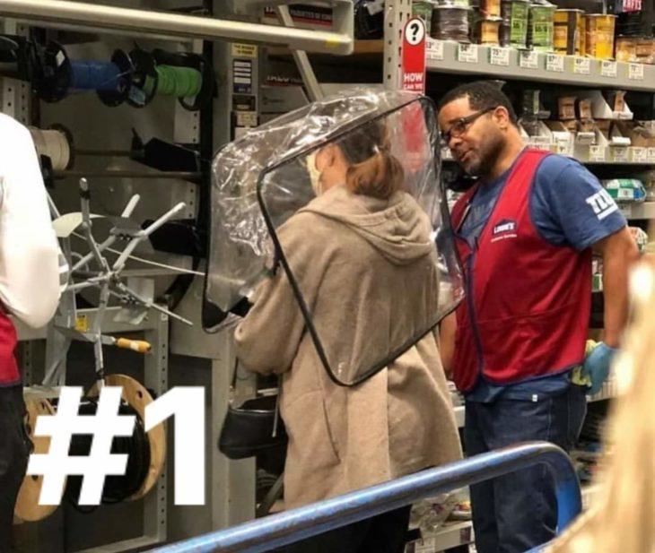 Señora en el supermercado usando una bolsa de edredón sobre la cabeza