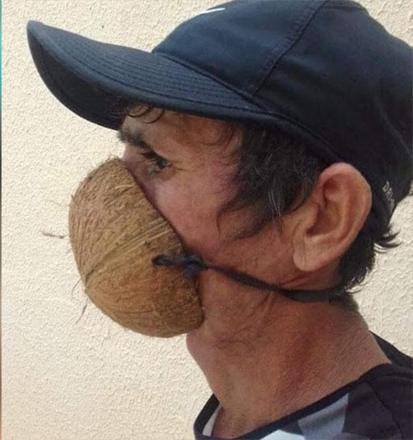 Señor con un coco como cubrebocas