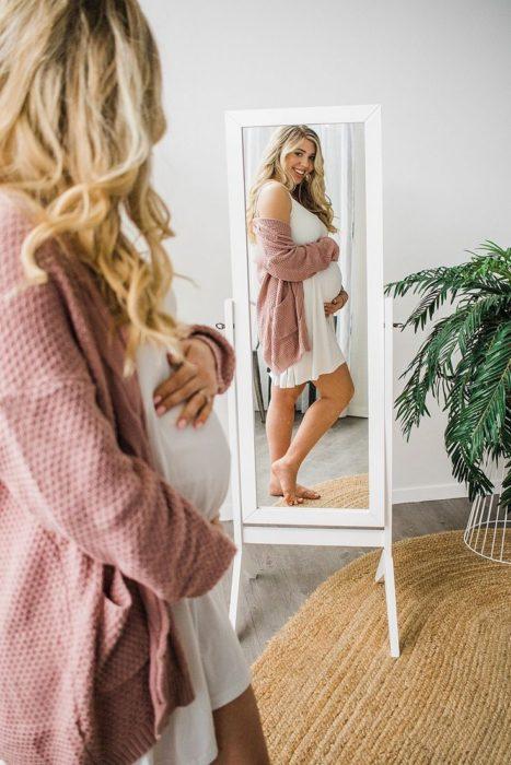 Mujer embarazada mirándose al espejo