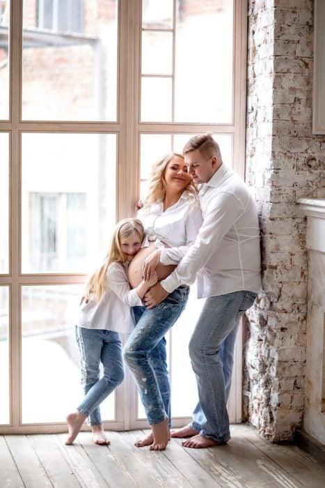 Familia posando para una foto en la que la esposa está embarazada