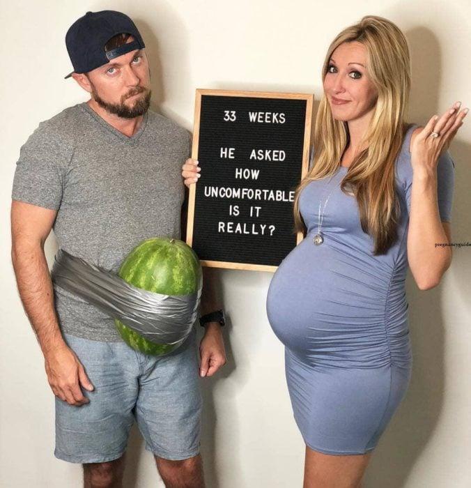 Mujer embarazada y pareja con una sandía pegada al abdomen