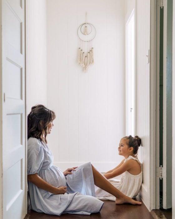 Mujer embarazada sentada en el piso junto con su hija