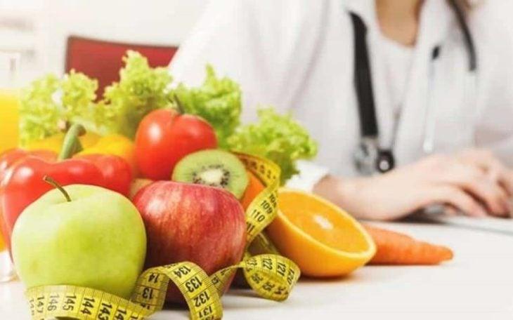 Nutriologoa sentada en su consultorio junto a una cesta de comida
