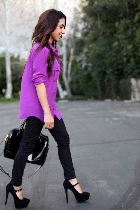 Chica con blusa morada y pantalón negro con tacones de plataforma
