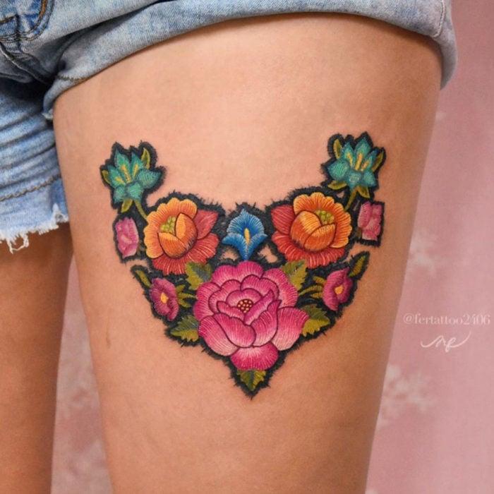 Fernanda Ramírez, tatuadora mexicana crea tatuajes bordados; flores rosas, azules y anaranjadas en la pierna