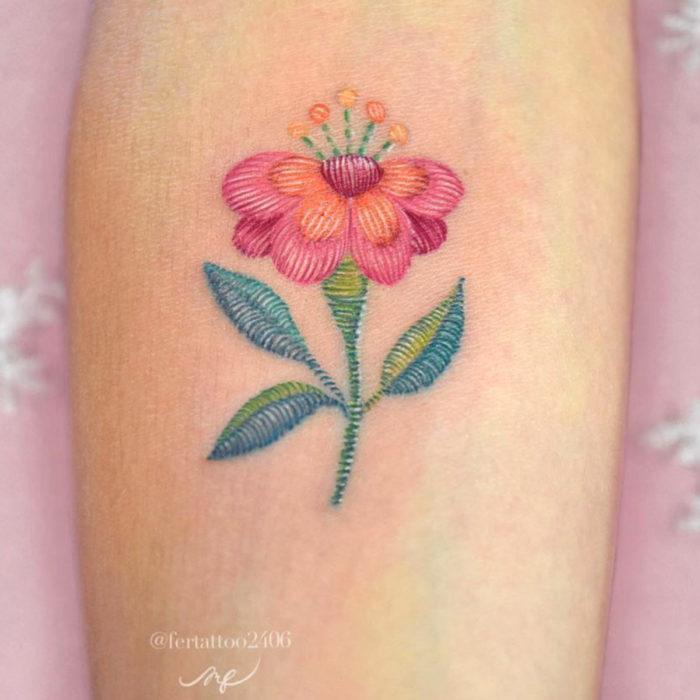 Fernanda Ramírez, tatuadora mexicana crea tatuajes bordados; flor rosa en el brazo