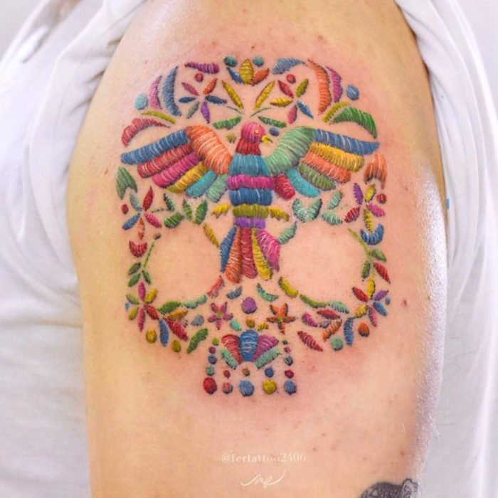Fernanda Ramírez, tatuadora mexicana crea tatuajes bordados; pájaro de colores con calavera en el brazo