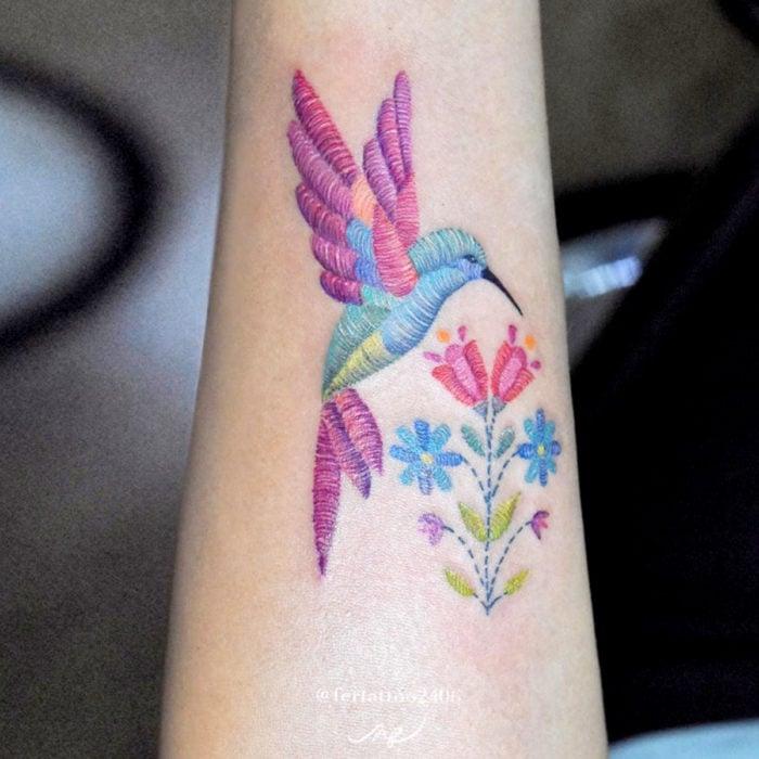 Fernanda Ramírez, tatuadora mexicana crea tatuajes bordados; colibrí con flores en el antebrazo