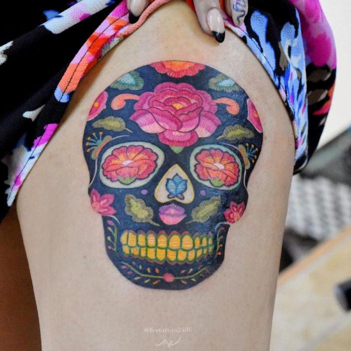 Fernanda Ramírez, tatuadora mexicana crea tatuajes bordados; calavera de día de muertos con flores en la pierna