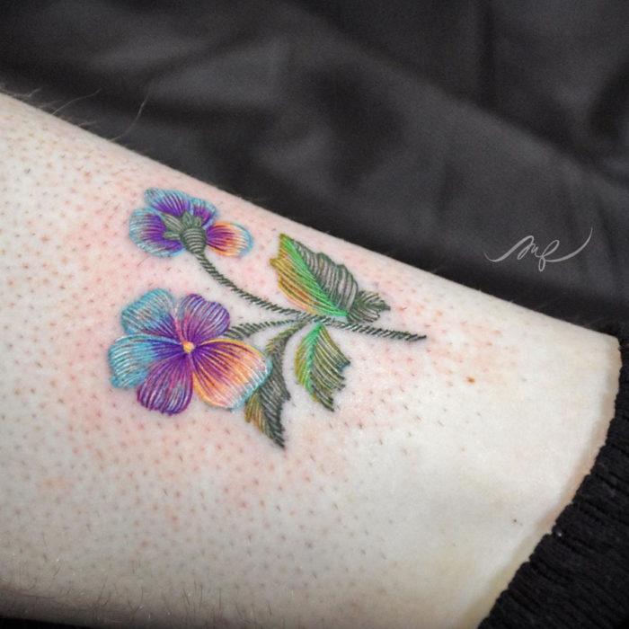 Fernanda Ramírez, tatuadora mexicana crea tatuajes bordados; flores pensamientos morados y azules en la pierna