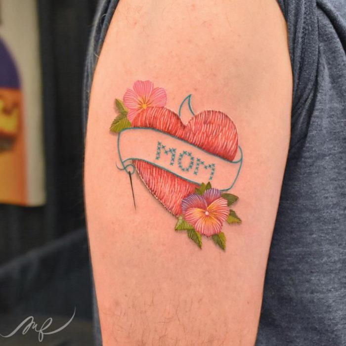 Fernanda Ramírez, tatuadora mexicana crea tatuajes bordados; corazón con la palabra mampa y flores pensamientos en el brazo