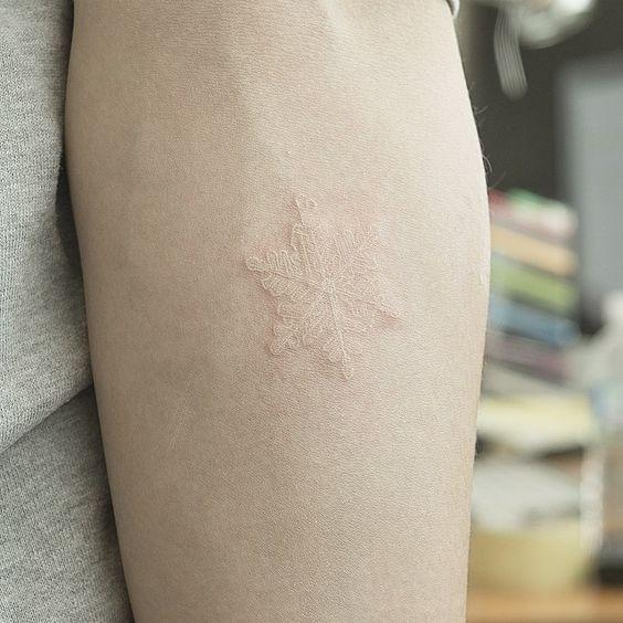 Tatuaje de copo de nieve con tinta blanca