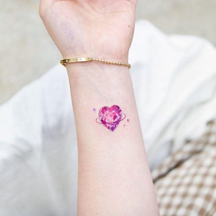 Tatuajes pequeños en la muñeca; corazón rosa de cristal