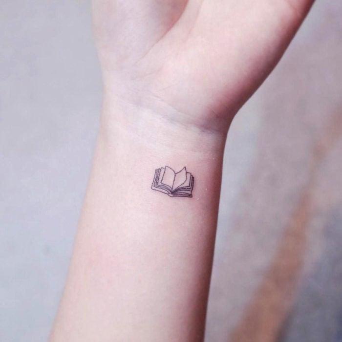 Tatuajes pequeños en la muñeca; libro abierto